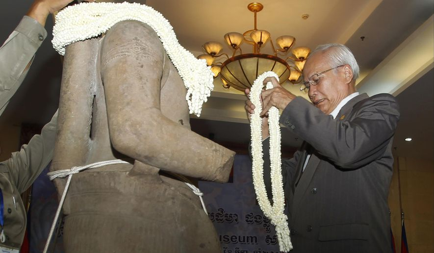 Cambodia's Secretary of State for the Ministry of Culture and Fine Arts Chuch Phoeun holds a bundle of jasmine to place onto the Torso of Rama, a 10th century stone statue, during a handing over ceremony in Phnom Penh, Cambodia, Monday, March 28, 2016. Cambodia welcomed home the stone statue, that was looted from a temple during the country's civil war, from Denver Art Museum in the United States. (AP Photo/Heng Sinith)