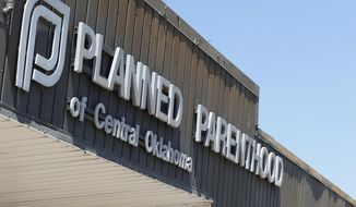 This July 24, 2015, file photo shows a sign at a Planned Parenthood Clinic in Oklahoma City. (AP Photo/Sue Ogrocki, File)