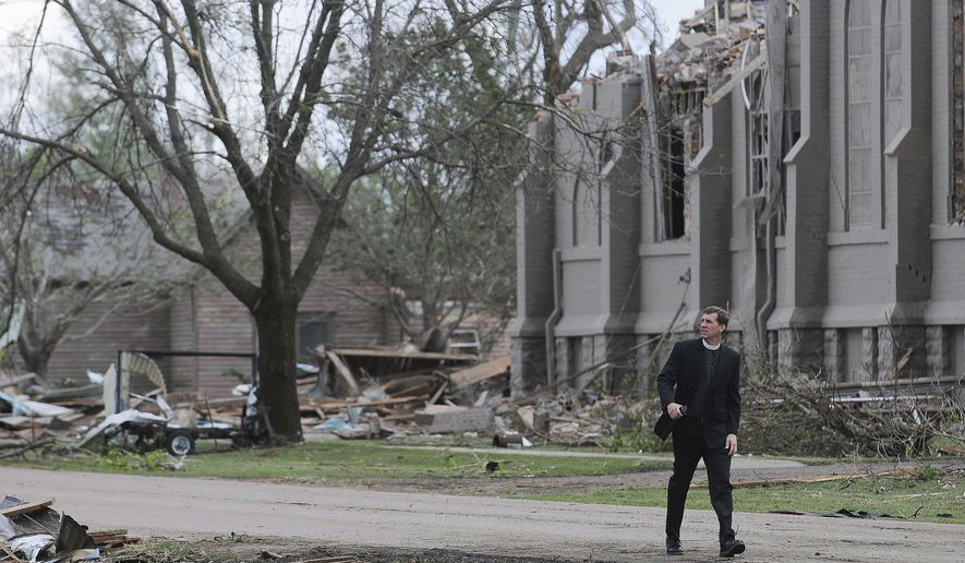 FILE - In this May 10, 2015 file photo, Rev. David Otten, from Immanuel Lutheran Church in Dimock, S.D., walks past Zion Lutheran Church in Delmont, S.D., after the church was destroyed by a tornado. Members of the church celebrated Easter in the town's community center, but they hope to be worshipping in a new church come Christmas. The final blueprint for a new church is being sent to five contractors for bids. The goal is to start construction sometime in April. (Joe Ahlquist/The Argus Leader via AP, File)  NO SALES; MANDATORY CREDIT