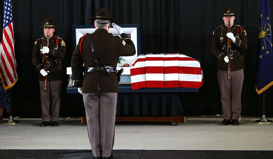 Howard County Deputies Justin Markley and Jake Gibson stand watch over the casket of coworker Deputy Carl Koontz at Northwestern Hiigh School in Kokomo, Ind., Monday, March 28, 2016.  Koontz was killed in the line of duty while serving a warrant on Maarch 20 in Russiaville. Koontz and Gibson worked together at the high school as resource officers. (Tim Bath/Kokomo Tribune via AP)