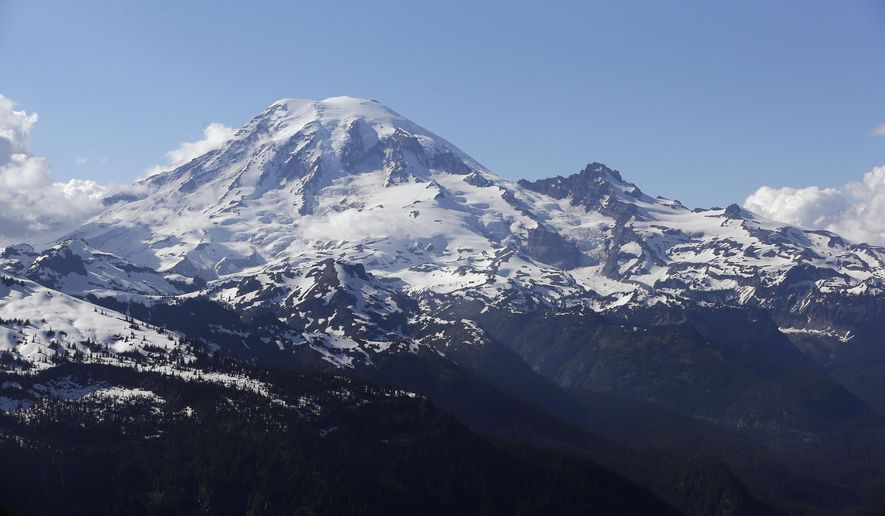 FILE -- In this file photo taken June 19, 2013, Mount Rainier is seen from a helicopter flying south of the mountain and west of Yakima, Wash. One climber has likely died from hypothermia and exposure on Mount Rainier after he and his climbing partner were caught in a winter storm over the weekend, a spokeswoman with Mount Rainier National Park said. A Chinook helicopter crew and other rescue teams were working Monday, March 28, 2016, to reach the 58-year-old man from Norway. (AP Photo/Elaine Thompson, File)