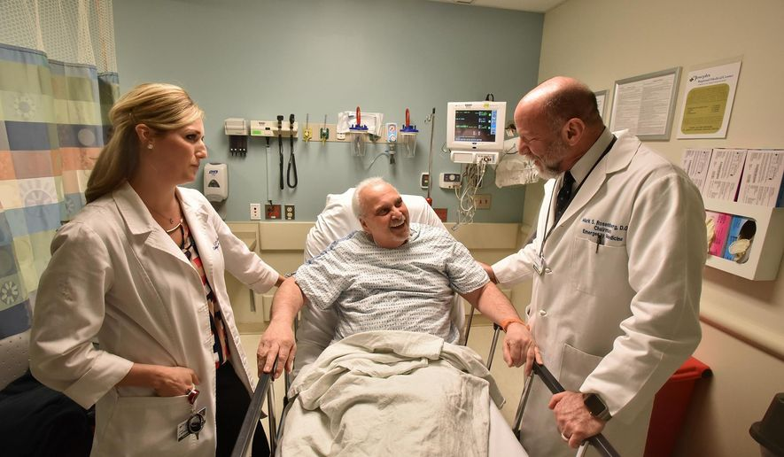 In this March 23, 2016, photo, Dr. Mark S. Rosenberg and Dr. Alexis LaPietra talk to patient Bob Notar in the emergency room at St. Joseph's Regional Medical Center in Paterson, N.J. The hospital has launched an opioid-alternative program to cut down on the abuse of the drugs that have helped to fuel a deadly crisis. (Marko Georgiev/The Record of Bergen County via AP) ONLINE OUT; MAGS OUT; TV OUT; INTERNET OUT;  NO ARCHIVING; MANDATORY CREDIT