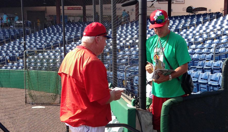 In this photo taken March 17, 2016, former Philadelphia Phillies manager Charlie Manuel, left, now a senior adviser for the team and a guest instructor in spring training, gives an autograph to a fan before the Phillies play the Tampa Bay Rays in a baeball game in Clearwater, Fla. From the minute Manuel walks onto the field, fans constantly seek his attention for pictures and autographs. (AP Photo/Rob Maaddi)
