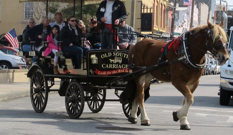 FILE - In this Feb. 17, 2016 file photo, a carriage moves through the City Market area in downtown Charleston, S.C. A federal judge has set an April, 19, 2016 hearing on a lawsuit challenging a requirement that tour guides who charge for their services in Charleston be required to pass both written and oral examinations. The plaintiffs in the lawsuit allege the requirements violate their First Amendment rights of freedom of speech. (AP Photo/Bruce Smith, file)