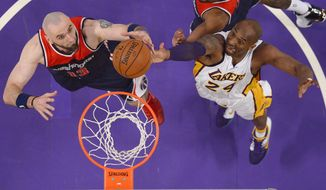 Washington Wizards center Marcin Gortat, left, of Poland, and Los Angeles Lakers forward Kobe Bryant reach for a rebound during the first half of an NBA basketball game, Sunday, March 27, 2016, in Los Angeles. (AP Photo/Mark J. Terrill)