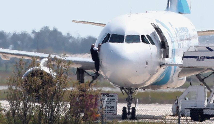 A man exits an EgyptAir jet through the pilot's window after an emergency landing at Larnaca airport in Cyprus on Tuesday. The hijacker eventually freed everyone aboard. (Associated Press)