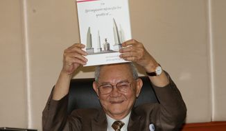 Chairman of the Constitution Drafting Commission Meechai Ruchupan holds the draft of new constitution during a press conference at the Parliament in Bangkok, Thailand, Tuesday. The junta chief said it will permit about 50 million eligible voters to vote on its constitution in a referendum on Aug. 7 (Associated Press)