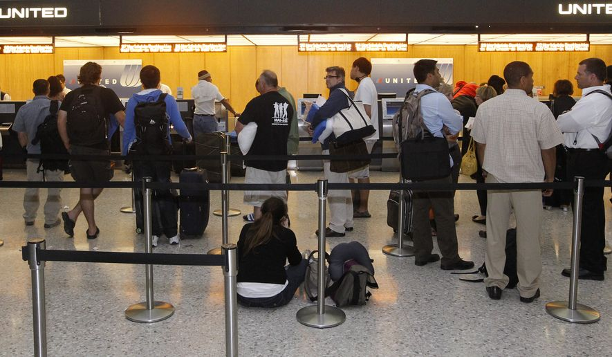 United Airlines passengers wait at the ticket counter of Washington Dulles International Airport in Chantilly, Va. (Associated Press)