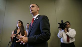 In this file photo taken Aug. 25, 2015, Republican presidential candidate Donald Trump's campaign manager Corey Lewandowski watches as Trump speaks in Dubuque, Iowa. (AP Photo/Charlie Neibergall)