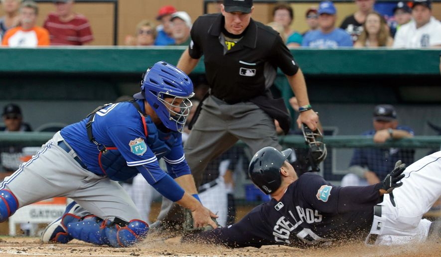 Toronto Blue Jays catcher Josh Thole, left, tags out Detroit Tigers' Nick Castellanos (9) at home plate in the third inning of a spring training baseball game, Tuesday, March 29, 2016, in Lakeland, Fla. (AP Photo/John Raoux)