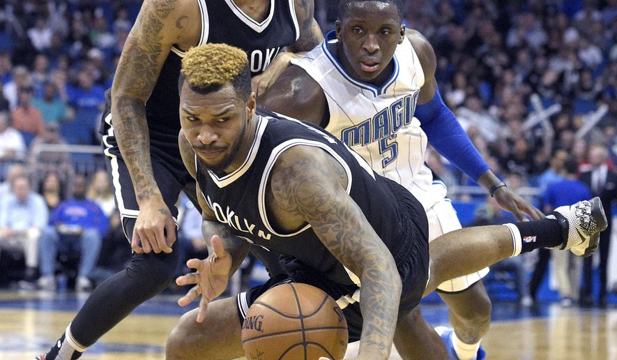 Brooklyn Nets guard Sean Kilpatrick falls to the ground after being fouled by Orlando Magic guard Victor Oladipo (5) as Nets forward Chris McCullough, rear, watches during the second half of an NBA basketball game in Orlando, Fla., Tuesday, March 29, 2016. The Magic won 139-105. (AP Photo/Phelan M. Ebenhack)