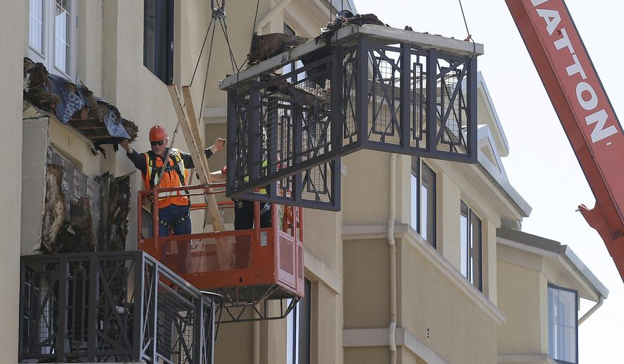 File - In this June 16, 2015, file photo, workers remove part of a balcony that collapsed at the Library Gardens apartment complex in Berkeley, Calif. A California prosecutor has decided against criminal charges over a balcony collapse in Berkeley last June that killed multiple students from Ireland. Alameda County District Attorney Nancy O'Malley said Tuesday, March 29, 2016, she made her decision after a nine-month investigation that drew in state officials and independent experts from the building industry. (AP Photo/Jeff Chiu, File)