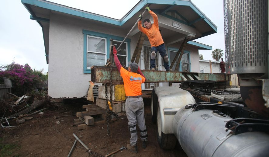 In this photo taken Monday, March 28, 2016, Adrian Lopez and Francisco Godina tighten the clamp holding a house onto its transport bed before hauling it away in Hillcrest, Calif. The home, built in 1925, was to be moved to a storage yard in Otay Mesa, Calif., before finally being relocated to a new lot in Chula Vista, Calif. The owner, Anne Wilson, had lived in the 800-square-foot stucco home for 23 years, plans to build a new three-story home on the lot.  (Peggy Peattie/The San Diego Union-Tribune via AP)  NO SALES; MANDATORY CREDIT