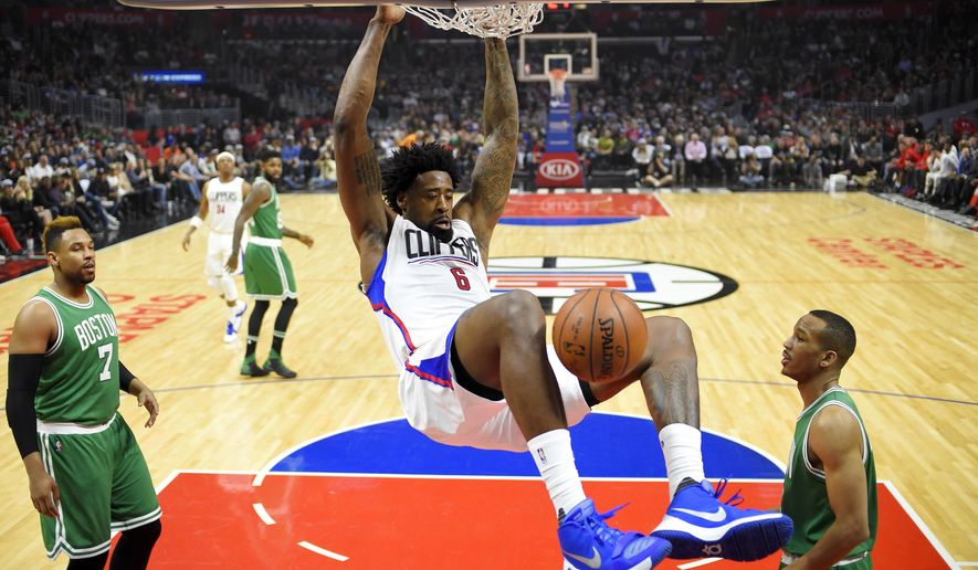 Los Angeles Clippers center DeAndre Jordan, center, dunks as Boston Celtics center Jared Sullinger, left, and guard Avery Bradley defend during the first half of an NBA basketball game, Monday, March 28, 2016, in Los Angeles. (AP Photo/Mark J. Terrill)