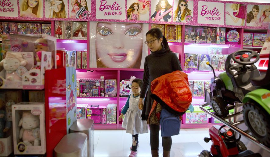 In this Saturday, Feb. 27, 2016, photo, a woman and child walk past a display of Barbie dolls at a store in Beijing, China. Sophisticated cyber-thieves tricked Mattel Inc., the Los-Angeles based maker of Barbie dolls into sending over $3 million to a Chinese bank account they controlled. Mattel's millions were swept up in a tide of dirty money that passes through China, which Western police are only beginning to understand. (AP Photo/Ng Han Guan)