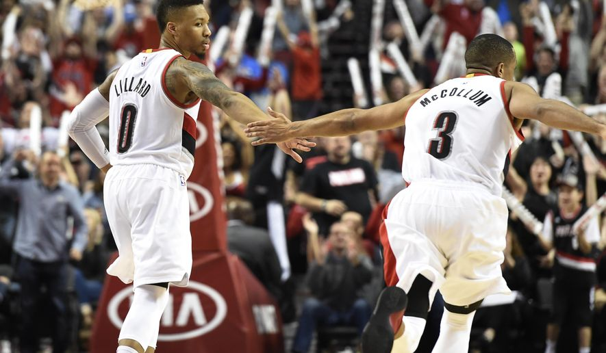 FILE - In this March 26, 2016, file photo, Portland Trail Blazers guard Damian Lillard (0) celebrates with teammate C.J. McCollum (3) after hitting a shot late in the fourth quarter of an NBA basketball game against the Philadelphia 76ers in Portland, Ore. Portland's backcourt duo of Damian Lillard and CJ McCollum are partners on the court and friends off it. Their almost symbiotic relationship has helped carry the surprising Trail Blazers into playoff position. (AP Photo/Steve Dykes, File)