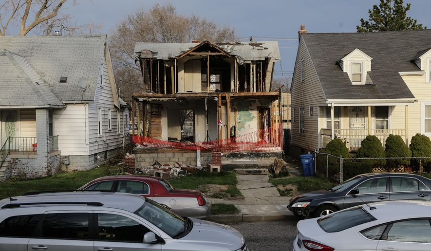 A Tuesday, March 22, 2016, photo shows the remains of an abandoned structure that artist Ryan Mendoza left behind for neighbors to deal with are seen in Detroit's west side, after tearing the shell off of the abandoned two-story house in Detroit and shipping the pieces overseas rebuilding it for display at Art Rotterdam in the Netherlands. Residents are upset with what they were left with and the safety of an exposed structure with nails, insulation wiring and destroyed pieces all through the yard and the structure. (Ryan Garza/Detroit Free Press via AP)  DETROIT NEWS OUT; TV OUT; MAGS OUT; NO SALES; MANDATORY CREDIT DETROIT FREE PRESS