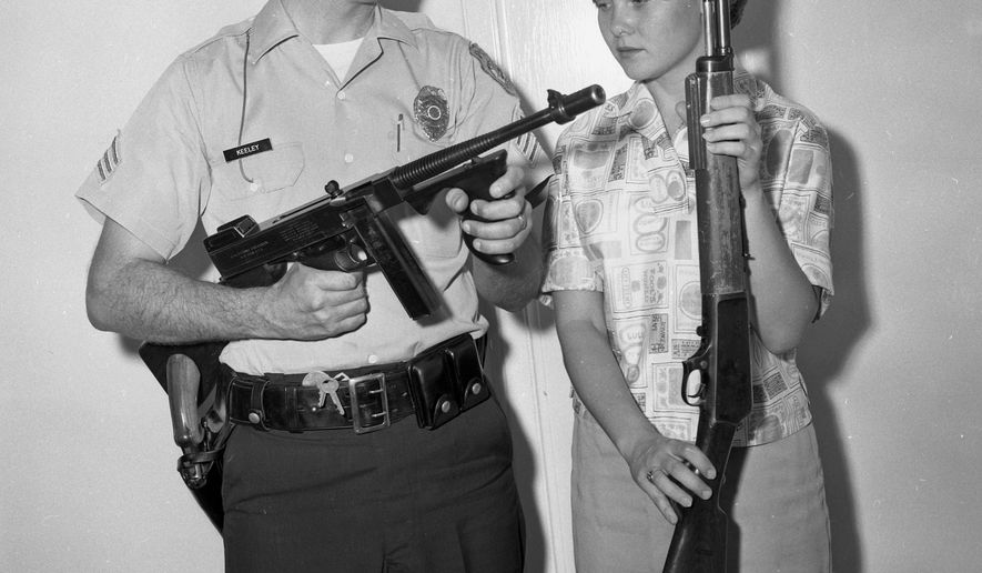 In this 1961 photo, Tucson Police Sgt. Tom Keeley holds a Colt Thompson submachine gun and secretary Linda Bradfield holds a Winchester Model 1907, with other guns confiscated from the John Dillinger gang during Dillinger's capture in Tucson, Ariz., in 1934. Police in Tucson are at odds with a small Indiana town over the Tommy gun taken from Dillinger during his arrest. The Arizona Daily Star reports that officials in Peru, Ind., want the Colt Thompson submachine gun turned over, saying they believe it was stolen from Peru police in 1933 before Dillinger was caught in Tucson. (Tucson Citizen Archive/Arizona Daily Star via AP) ALL LOCAL TELEVISION OUT; PAC-12 OUT; MANDATORY CREDIT;  GREEN VALLEY NEWS OUT