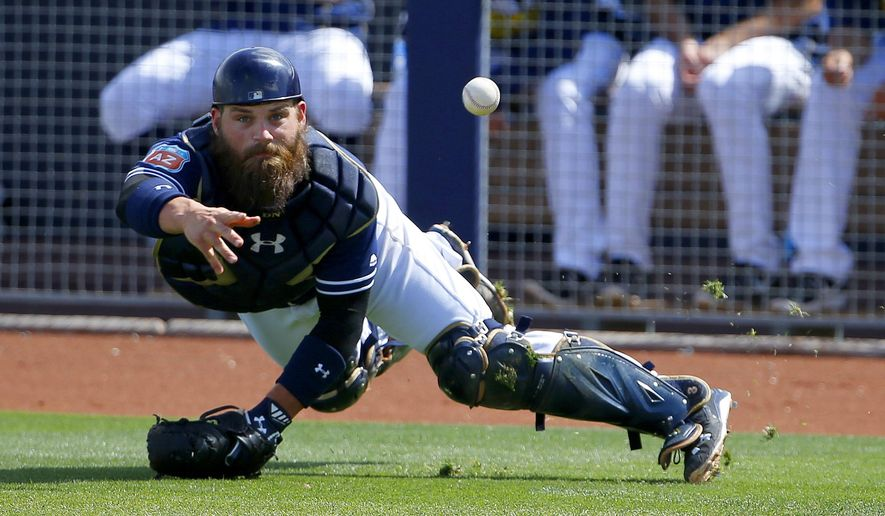 San Diego Padres' Derek Norris tosses the baseball to pitcher Colin Rea covering home plate after a pitch got away from Norris during the fourth inning of a spring training baseball game Tuesday, March 29, 2016, in Peoria, Ariz.  Los Angeles Dodgers runner Chase Utley scored a run on the play. (AP Photo/Ross D. Franklin)