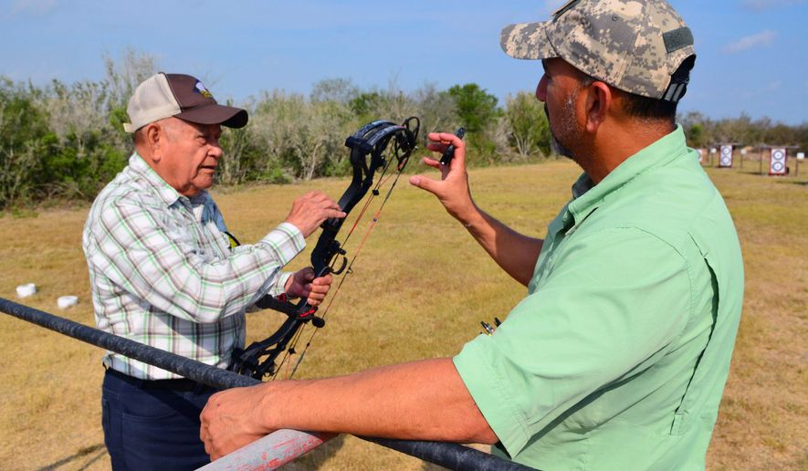 In this photo taken March 6, 2016, Rudy Garza, left, of Eagles Nest Archery, talks about bows with Juan De Leon at the Golden Eagle Field Archery Range near La Feria, Texas. De Leon is president of the club. (Rick Kelley/Valley Morning Star via AP) MANDATORY CREDIT