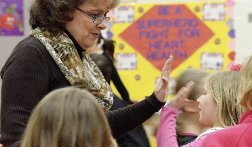 In this March 2, 2016 photo, Rosemary Martin, a long-time physical education teacher at Heyworth Elementary School in Heyworth, Ill., high-fives second-grader Kamryn Whitwood in the school gym during a P.E. class. Martin has a long-standing practice of integrating heart health lessons into P.E. class. She has decorated the gym walls with posters promoting heart health. (Steve Smedley/The Pantagraph via AP) MANDATORY CREDIT