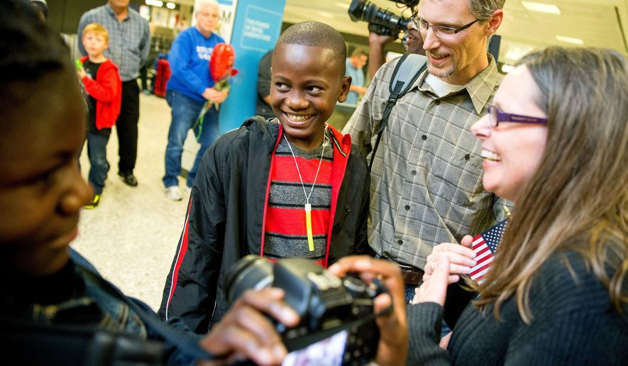 In this Nov. 11, 2015, file photo, Jennifer and Eric Sands of Illinois, right, accompanied by their adopted daughter Joy, 12, left, smile as their adopted son Issac, 12, center arrives from Congo at Dulles International Airport, in Dulles, Va. (AP Photo/Andrew Harnik, File)