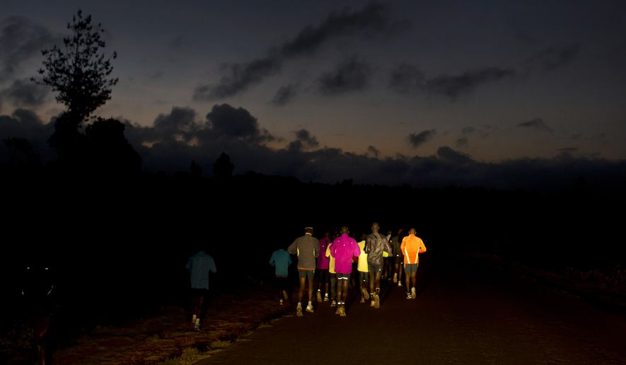 In this Jan. 30, 2016, photo Kenyan athletes are illuminated by car headlights as they train on a country road before dawn, near the village of Kaptagat in western Kenya. (AP Photo/Ben Curtis)