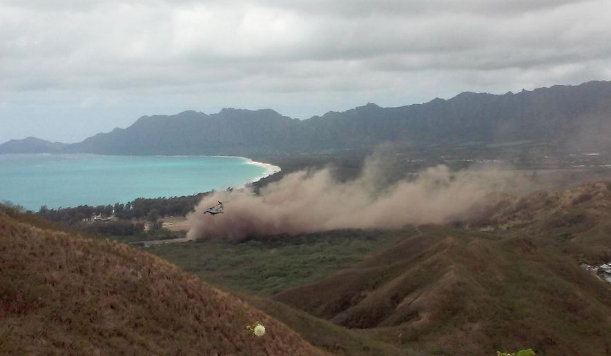 FILE- This May 17, 2015 file photo shows debris rising as a Marine Corps Osprey aircraft, not pictured, makes a hard landing on Bellows Air Force Station near Waimanalo, Hawaii. The parents of a Marine killed in the crash of an Osprey hybrid aircraft in Hawaii last year are suing the aircraft's manufacturers and unnamed government agencies and the lawsuit was filed Monday, March 28, 2016. (AP Photo/Kimberly Hynd, File)