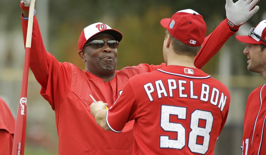 "FILE - In this Feb. 20, 2016, file photo, Washington Nationals manager Dusty Baker greets relief pitcher Jonathan Papelbon (58) during a spring training baseball workout, in Viera, Fla. When managing the Cincinnati Reds, Dusty Baker always had a dream about winning a World Series in red. He's back in red with the Washington Nationals as the ""worldly"" baseball lifer returns for ""one last album.""(AP Photo/John Raoux, File)"