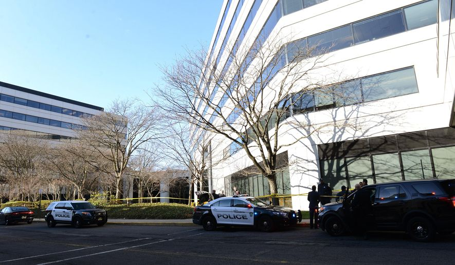 Police investigate the scene where a body was found on the grassy area in the rear of the Glenpointe business complex Tuesday, March 29, 2016, in Teaneck, N.J.   (Tariq Zehawi /The Record of Bergen County via AP) ONLINE OUT; MAGS OUT; TV OUT; INTERNET OUT;  NO ARCHIVING; MANDATORY CREDIT
