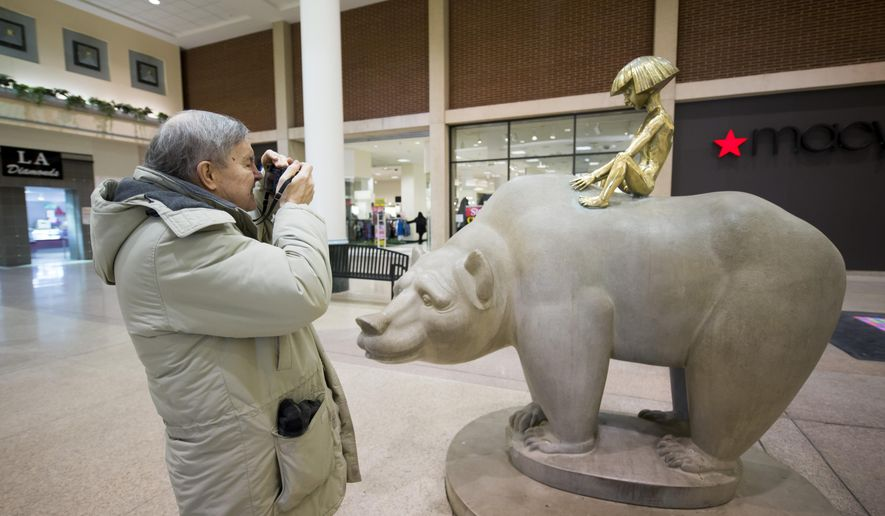 "FILE - In this Feb. 25, 2015 file photo, Bill Yagerlener takes a picture of the sculpture ""Bear and Boy"", by Marshall Fredericks at Northland mall in Southfield, Mich.  A suburban Detroit arts commission has started a fundraising campaign to recoup money spent on the sculpture displayed at the popular shopping mall for more than 60 years.   (David Guralnick/Detroit News via AP)  DETROIT FREE PRESS OUT; HUFFINGTON POST OUT; MANDATORY CREDIT"
