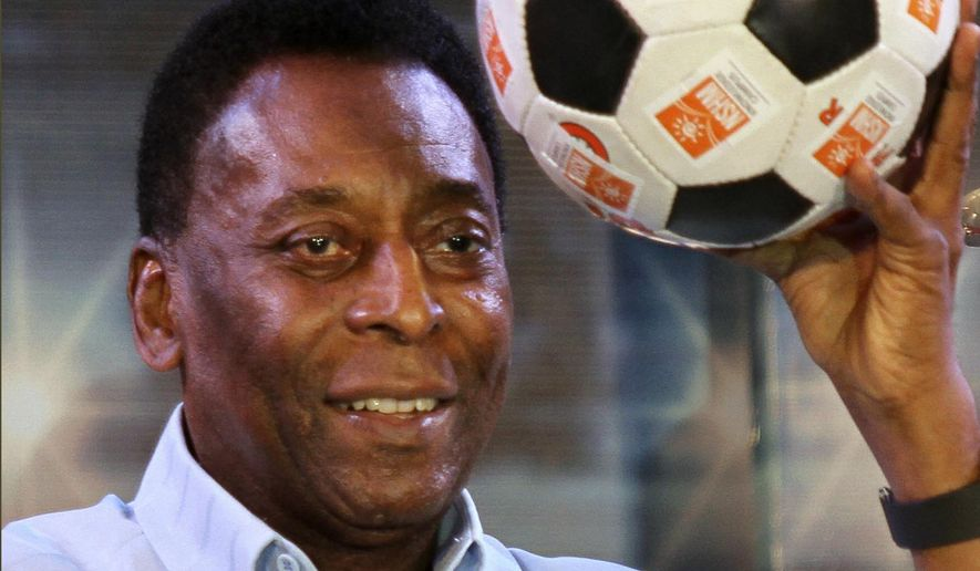 FILE - In this Oct. 12, 2015 file photo, Brazilian football legend Pele poses with a football during an interaction session with students in Kolkata, India. Pele is suing Samsung in Chicago federal court, claiming the electronics company improperly used his identity in The New York Times. The lawsuit claims Samsung used a Pele look-alike in an October advertisement for televisions after breaking off negotiations to use Pele's image. The lawsuit says the ad will confuse consumers and hurt the value of his endorsement rights. It seeks $30 million in damages. (AP Photo/Bikas Das File)