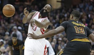 Houston Rockets' James Harden, left, passes against Cleveland Cavaliers' Tristan Thompson during the first half of an NBA basketball game Tuesday, March 29, 2016, in Cleveland. (AP Photo/Tony Dejak)