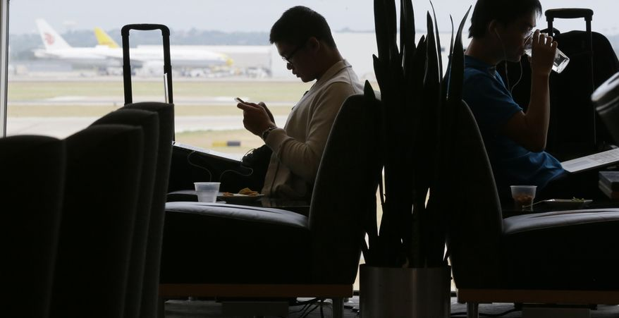 In this Thursday, Aug. 26, 2015, photo, air travelers wait in the Admiral's Club at the Dallas-Fort Worth International Airport in Grapevine, Texas. As families and individuals start to book summer travel, a debate is rising about whether airlines make it too hard to choose the most affordable options. (AP Photo/LM Otero, File)