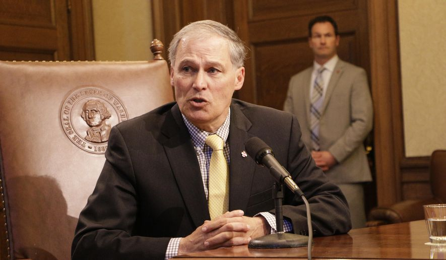 Washington Gov. Jay Inslee talks to the media about his decision to ban non-essential state travel to North Carolina following a new law related to transgender access Tuesday, March 29, 2016, in Olympia, Wash. The North Carolina law prevents local governments from protecting people based on sexual orientation and gender identity when they use public accommodations such as hotels. (AP Photo/Rachel La Corte)