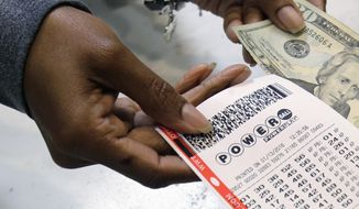 A clerk hands over a Powerball ticket in exchange for cash at Tower City Lottery Stop in Cleveland. (Associated Press)