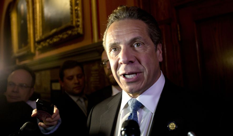 New York Gov. Andrew Cuomo talks to media members outside his office at the state Capitol on Wednesday, March 30, 2016, in Albany, N.Y. (AP Photo/Mike Groll)