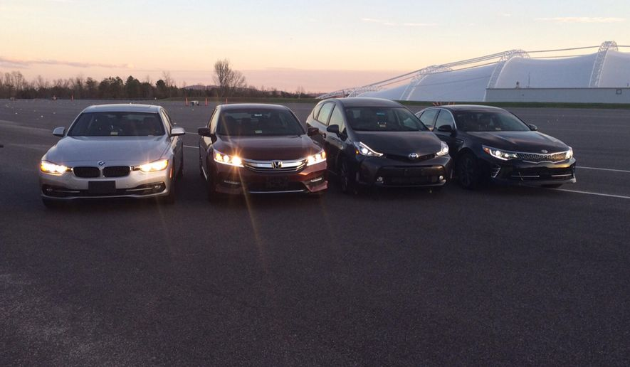 """In this photo provided by the The Insurance Institute for Highway Safety, from left, a BMW 3 series, Honda Accord, Toyota Prius V and a Kia Optima are seen at the institute's Vehicle Research Center in Ruckersville, Va. A new study that rates the headlights of more than 30 midsized car models found only one model earned a """"good"""" rating. Of the rest, half were rated """"acceptable"""" and half were rated """"poor."""" The difference between the top-rated and bottom-rated model in terms of a driver's ability to see down a dark road was substantial. (Russ Rader/Insurance Institute for Highway Safety via AP)"""