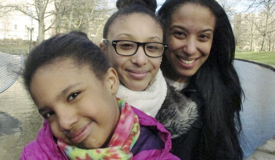In this Monday, March 21, 2016 photo, Adelaida Torres, right, poses with daughters Elizabeth, left, and Gloria, center, in Hartford, Conn. Torres believes she never would have won custody of her two daughters in 2013 during a bitter court fight with her now-ex-husband if not for the free legal help from attorney Linda Allard and Greater Hartford Legal Aid. Connecticut lawmakers are considering a bill that would create a task force to look into expanding the right to free lawyers for the poor in civil cases. (AP Photo/Dave Collins)