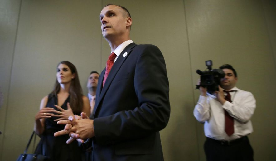 Republican presidential candidate Donald Trump's campaign manager Corey Lewandowski watches as Trump speaks in Dubuque, Iowa. Florida police have charged Lewandowski with simple battery in connection with an incident earlier in the month involving a reporter. (AP Photo/Charlie Neibergall)