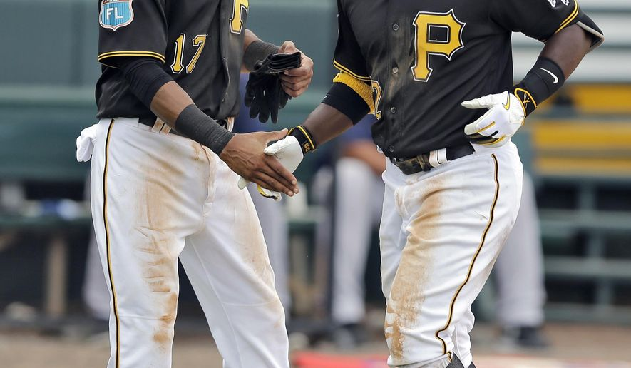 Pittsburgh Pirates' Andrew McCutchen, right, shakes hands with Pedro Florimon after hitting a two-run home run off Boston Red Sox's Rob Wort during the seventh inning of a spring training baseball game Wednesday, March 30, 2016, in Bradenton, Fla. (AP Photo/Chris O'Meara)
