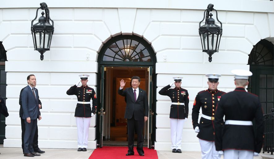 In this file photo, Chinese president Xi Jinping, center, waves after he is greeted by Ambassador Peter A. Selfridge, left, Chief of Protocol of the United States, upon his arrival at the White House in Washington, Thursday, March 31, 2016.  (Andrew Harnik/AP) **FILE**