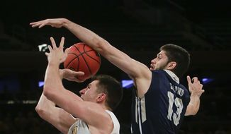 George Washington's Patricio Garino (13) defends Valparaiso's Alec Peters (25) during the first half of an NCAA college basketball game in the final of the NIT on Thursday, March 31, 2016, in New York. (AP Photo/Frank Franklin II)
