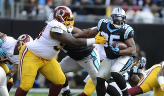 "FILE - In this Nov. 22, 2015, file photo, Carolina Panthers' Jonathan Stewart (28) tries to run past Washington Redskins' Terrance Knighton (98) in the first half of an NFL football game in Charlotte, N.C.  After seeing their team unravel following a disputed penalty call in a 28-point loss this season, a couple of veterans on the Redskins  safety Dashon Goldson and nose tackle Terrance ""Pot Roast"" Knighton thought a players-only meeting would be a good idea. (AP Photo/Mike McCarn, File)"