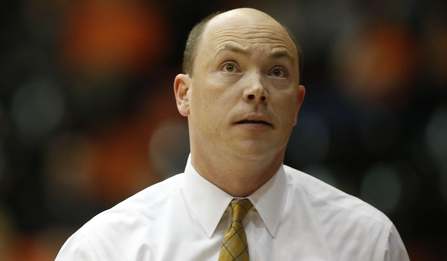 George Washington head coach Jonathan Tsipis looks at the score board during the first half of a college basketball game against Gonzaga in the first round of the NCAA tournament, in Corvallis, Ore.,  on Friday, March 20, 2015. (AP Photo/Timothy J. Gonzalez)