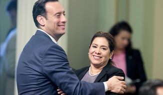 Assemblyman Roger Hernandez, West Covina Democrat and Assemblywoman Nora Campos, San Jose Democrat, celebrate after a bill to raise the state's minimum wage was approved by the Assembly on Thursday in Sacramento, Calif. (Associated Press)