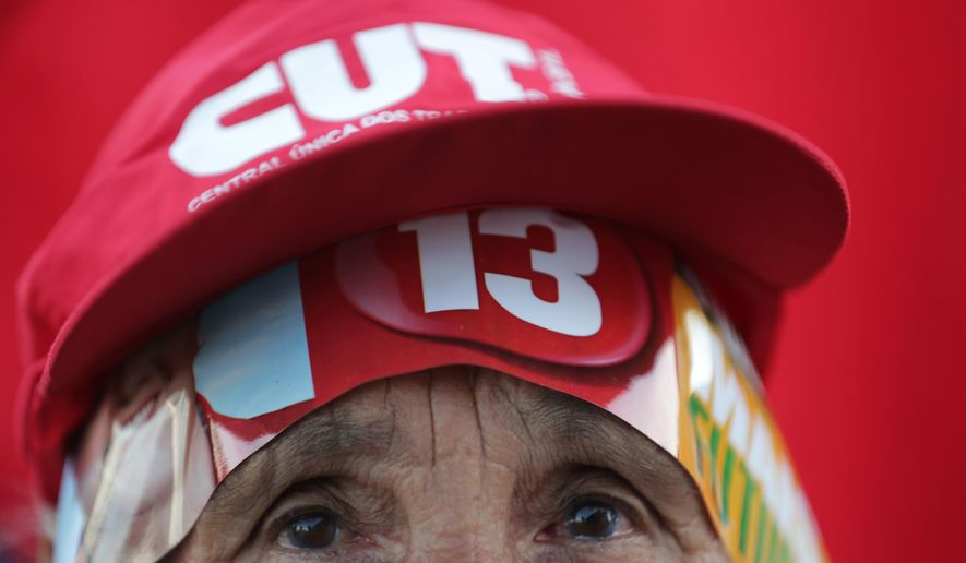 A government supporter wears the number 13 on her cap, the number associated with the ruling Workers Party, as people rally in support of Brazil's President Dilma Rousseff and former President Luiz Inacio Lula da Silva in Brasilia, Brazil, Thursday, March 31, 2016. Rousseff is facing impeachment proceedings as her government faces a stalling national economy and multiple corruption scandals. (AP Photo/Eraldo Peres)
