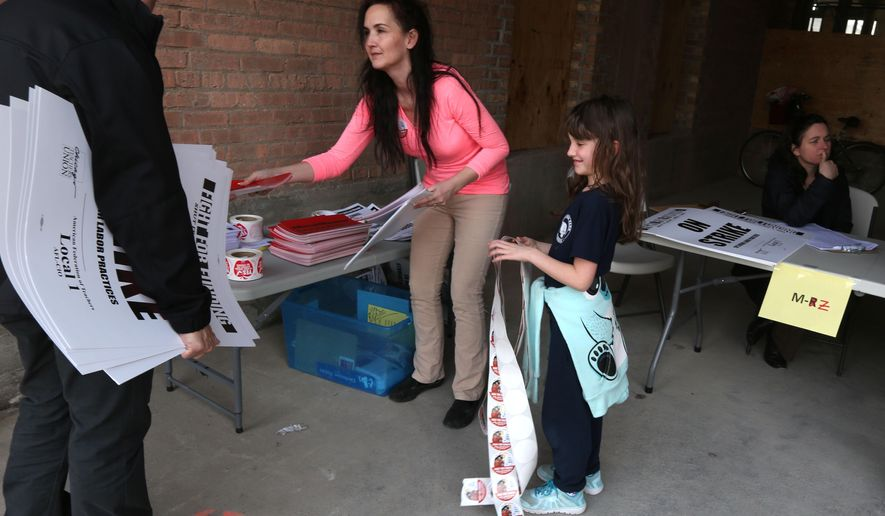 In this Wednesday, March 30, 2016 photo, seventh-grade teacher Katherine Gallingly, of Portage Park Elementary School, center, and her daughter, Caitlin, 7,  assist with signs at the Chicago Teachers Union headquarters in Chicago and in preparation for Friday's one-day teachers strike. The teachers union and other community groups and unions are calling for more state funding for schools and social services. (Phil Velasquez /Chicago Tribune via AP))