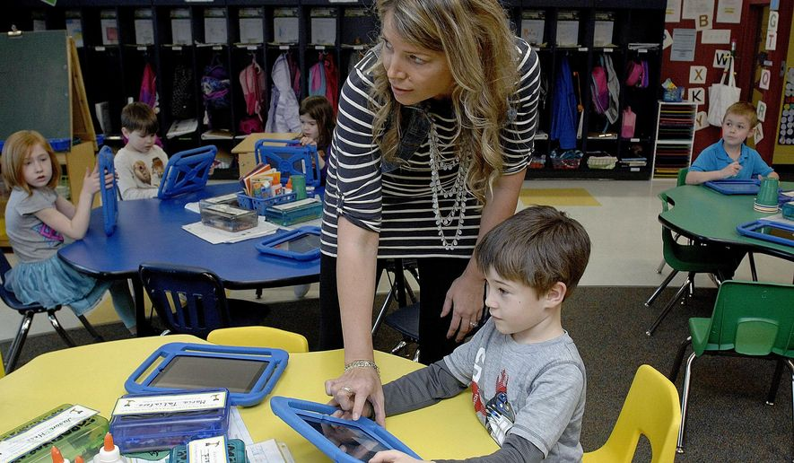 ADVANCE FOR USE SATURDAY, APRIL 2 AND THEREAFTER - In this March 13, 2016 photo, Olympia North Elementary School kindergarten teacher Laura Baner puts Gavin Ballard's work on the video board from his work on the iPad during class in rural Stanford, Ill. (Lori Ann Cook-Neisler/The Pantagraph via AP) MANDATORY CREDIT