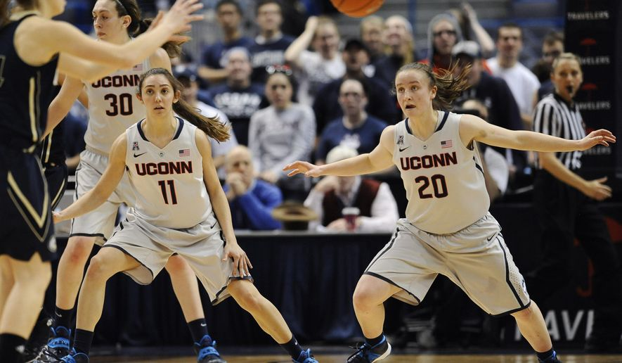 FILE - In this Dec. 5, 2013, file photo, Connecticut's Briana Pulido (11), and Tierney Lawlor (20) defend against UC Davis during the second half of an NCAA college basketball game in Hartford, Conn. After walking on to the team three years ago, the pair, now on scholarship will be looking for their third national titles as the Huskies go for their fourth in a row. (AP Photo/Jessica Hill, File)
